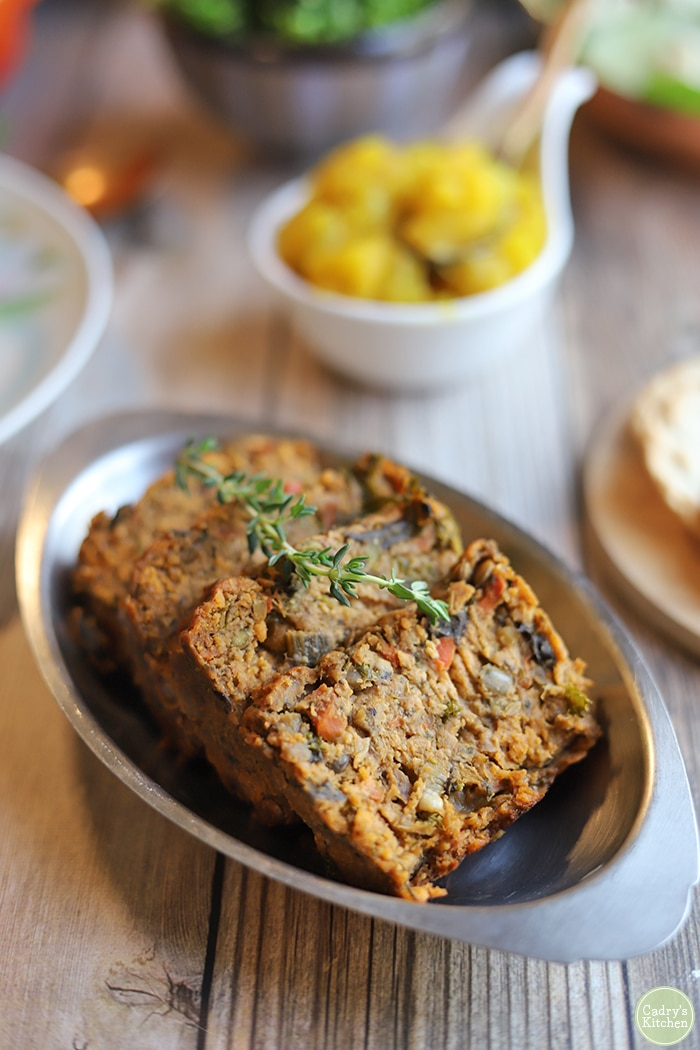 Sliced lentil loaf on metal serving dish.