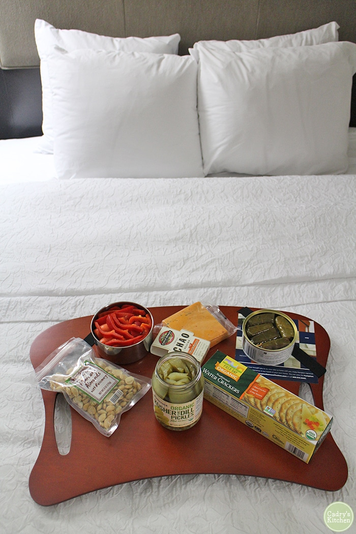 Hotel bed with tray holding crackers, non-dairy cheese, pickles, dolmas, and vegetables.