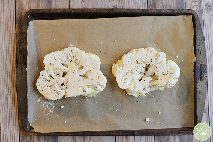 Vegan cauliflower steaks on a baking sheet with parchment paper.