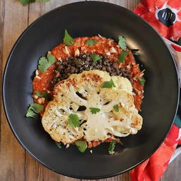 Cauliflower steak in black bowl with French lentils and romesco sauce.
