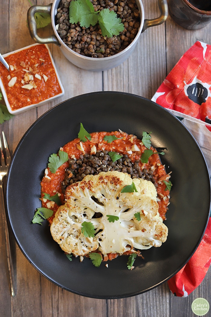 Overhead vegan cauliflower steaks in black bowl with romesco sauce and French lentils du Puy.