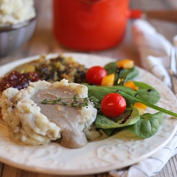 Plate with mashed potatoes, chestnut gravy, spinach salad, and vegan turkey.