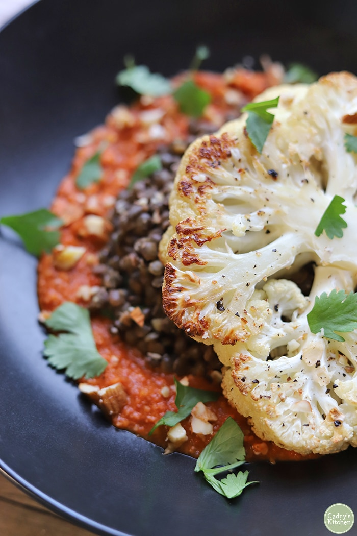 Close-up roasted cauliflower steak with lentils and romesco sauce in black bowl.