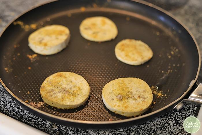Eggy tofu circles in skillet.