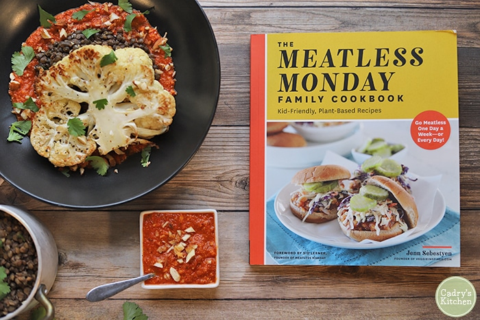 Meatless Monday cookbook by a bowl with vegan cauliflower steaks, lentils, and romesco sauce.