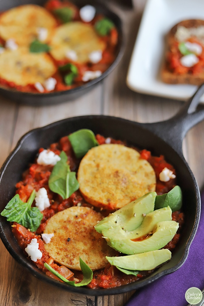 Vegan shakshuka in skillet with avocado.