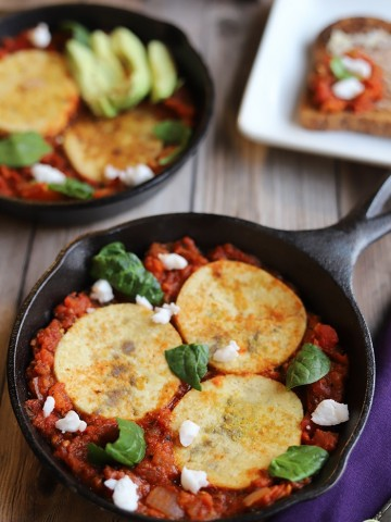 Eggy tofu circles in tomato & bell pepper sauce in skillet.