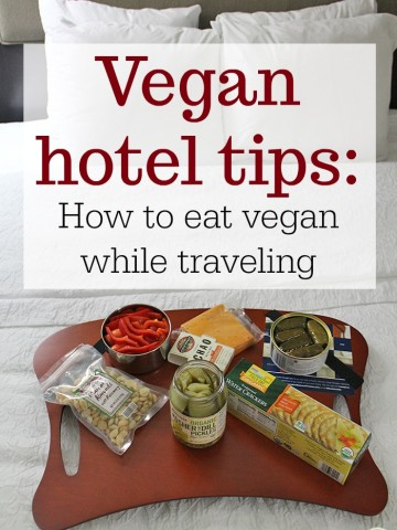 Text inlay: Vegan hotel tips: How to eat vegan while traveling. Tray with vegan cheese, crackers, and snacks on bed.