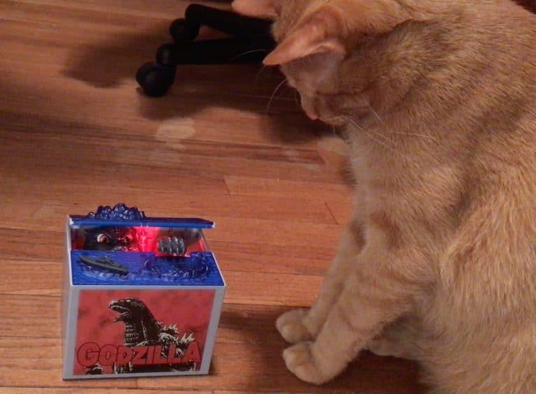 Avon the cat watching Godzilla bank.