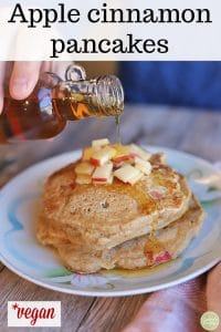 Text overlay: Apple cinnamon pancakes. Vegan. Syrup being poured onto stack of pancakes.