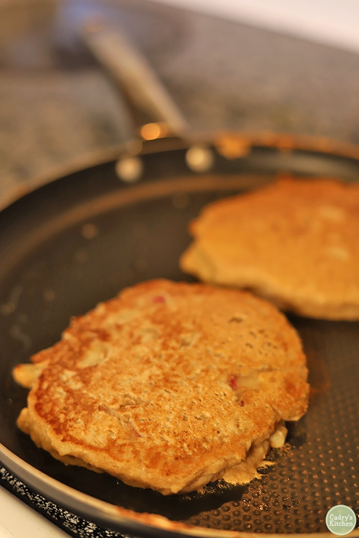 Whole wheat apple cinnamon pancakes cooking in skillet.