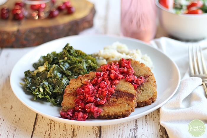Field Roast seitan with cranberry salsa, collard greens, and mashed potatoes on plate.