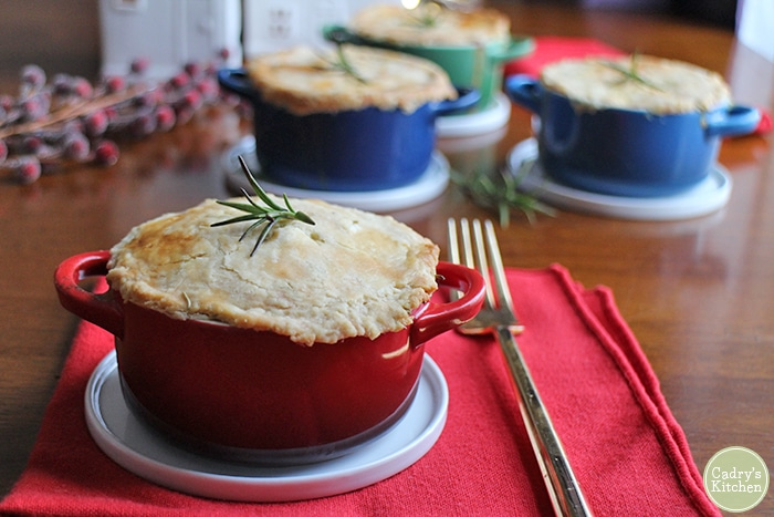 Mini vegetable pot pies on table with red napkin for vegan Christmas dinner.