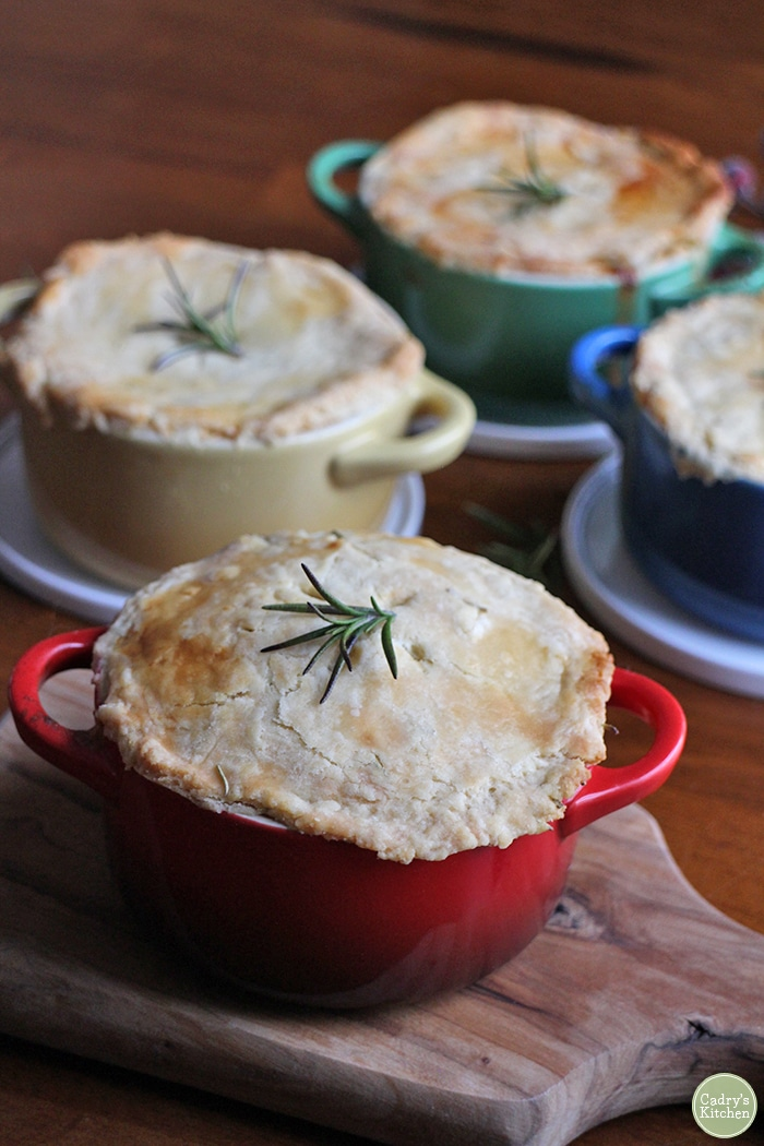 Mini vegetable pot pies on table for vegan Christmas dinner in Le Creuset mini casserole dishes.