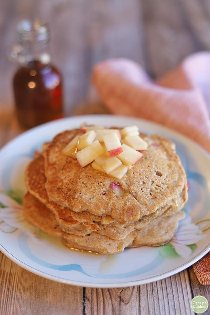 Stack of apple cinnamon pancakes on plate.
