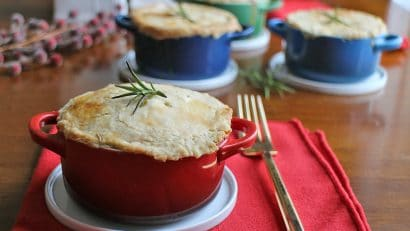 Individual pot pies in cocottes on table.