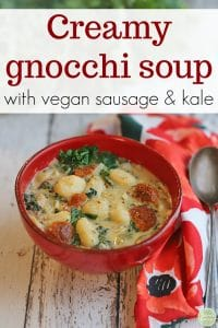 Text overlay: Creamy gnocchi soup with vegan sausage & kale. Red bowl of soup with colorful napkin.
