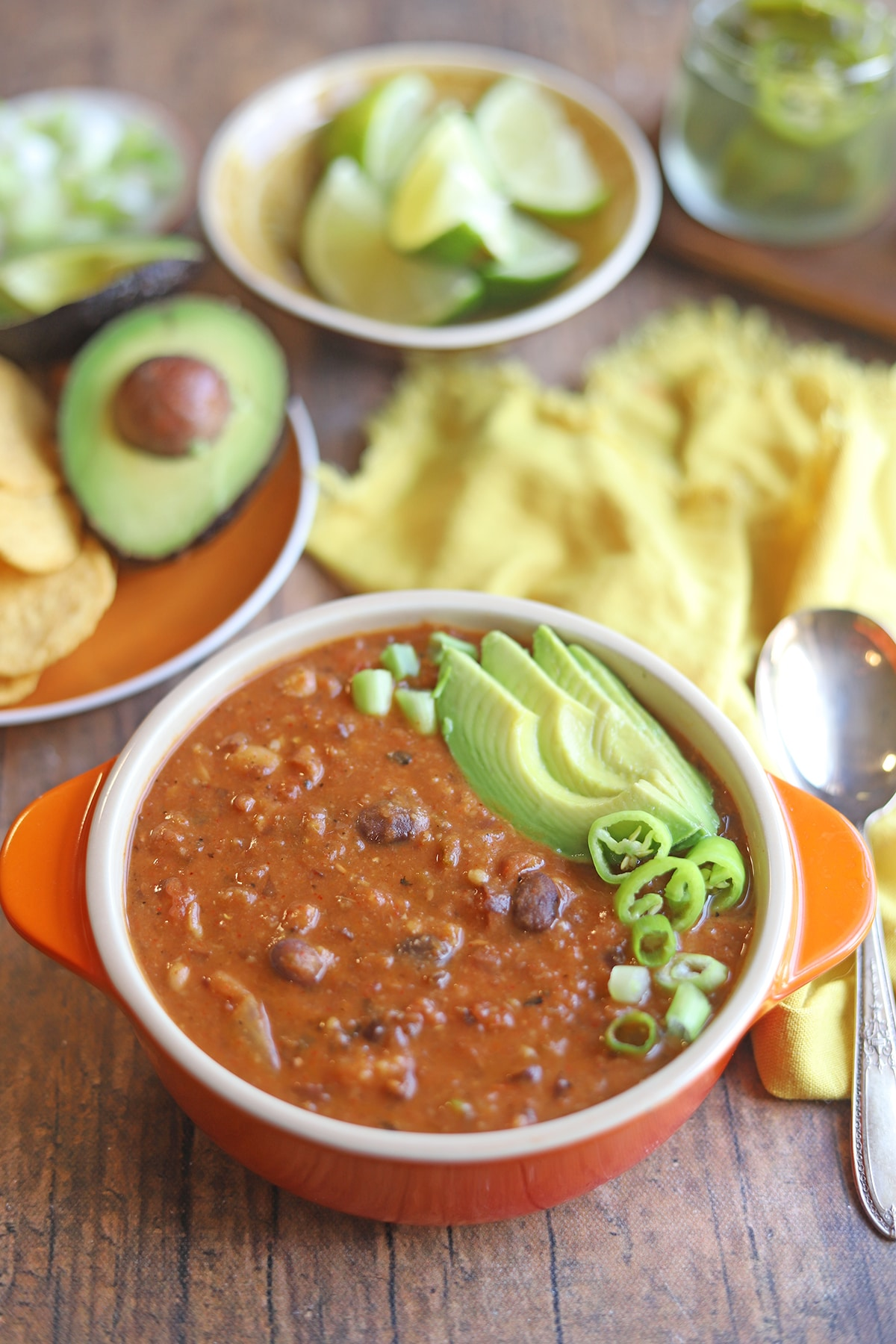 Orange bowl with chili by avocado, limes, and yellow napkin.