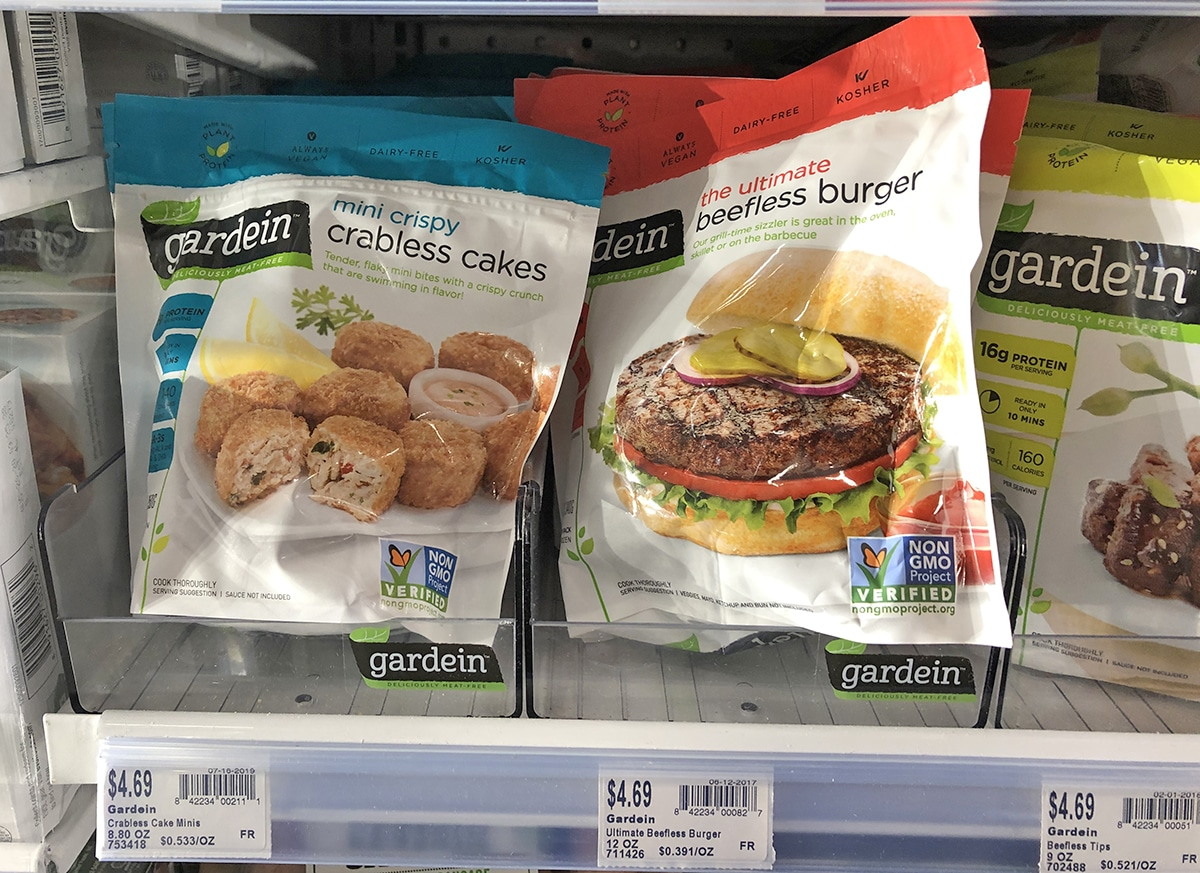 Package of Gardein crabless cakes and beefless burgers in grocery store freezer.