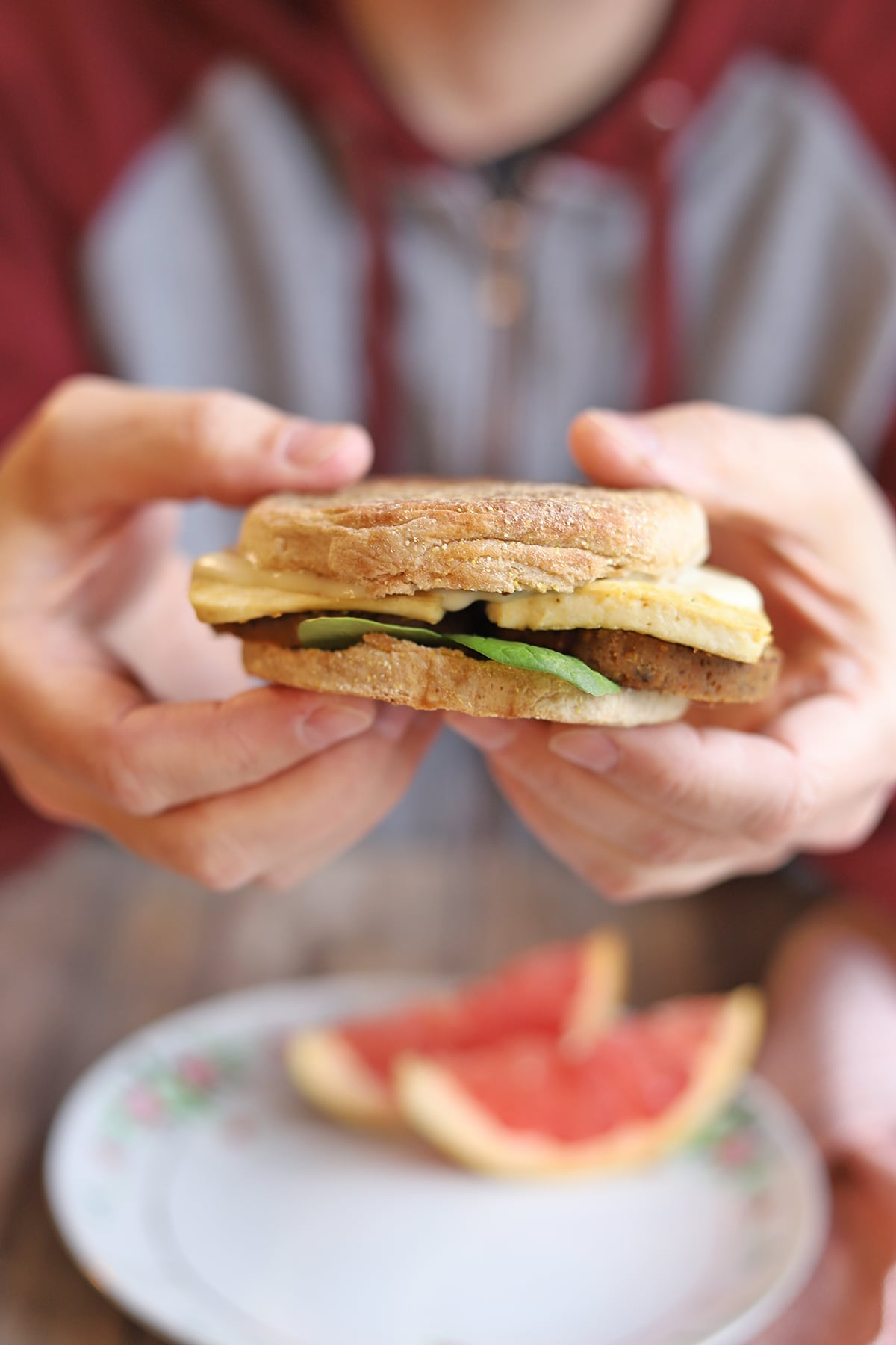 Hands holding English muffin breakfast sandwich.