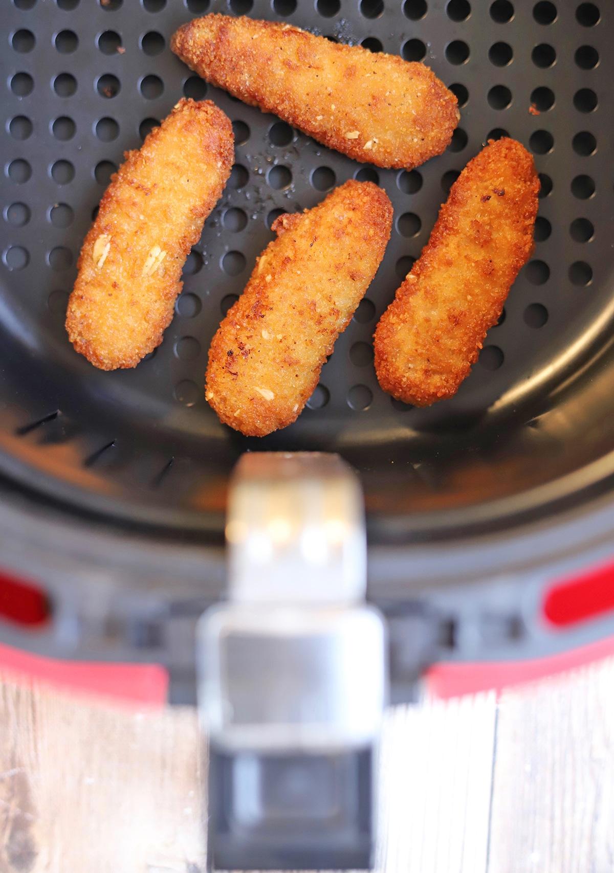 Trader Joe's chickenless strips in air fryer basket.