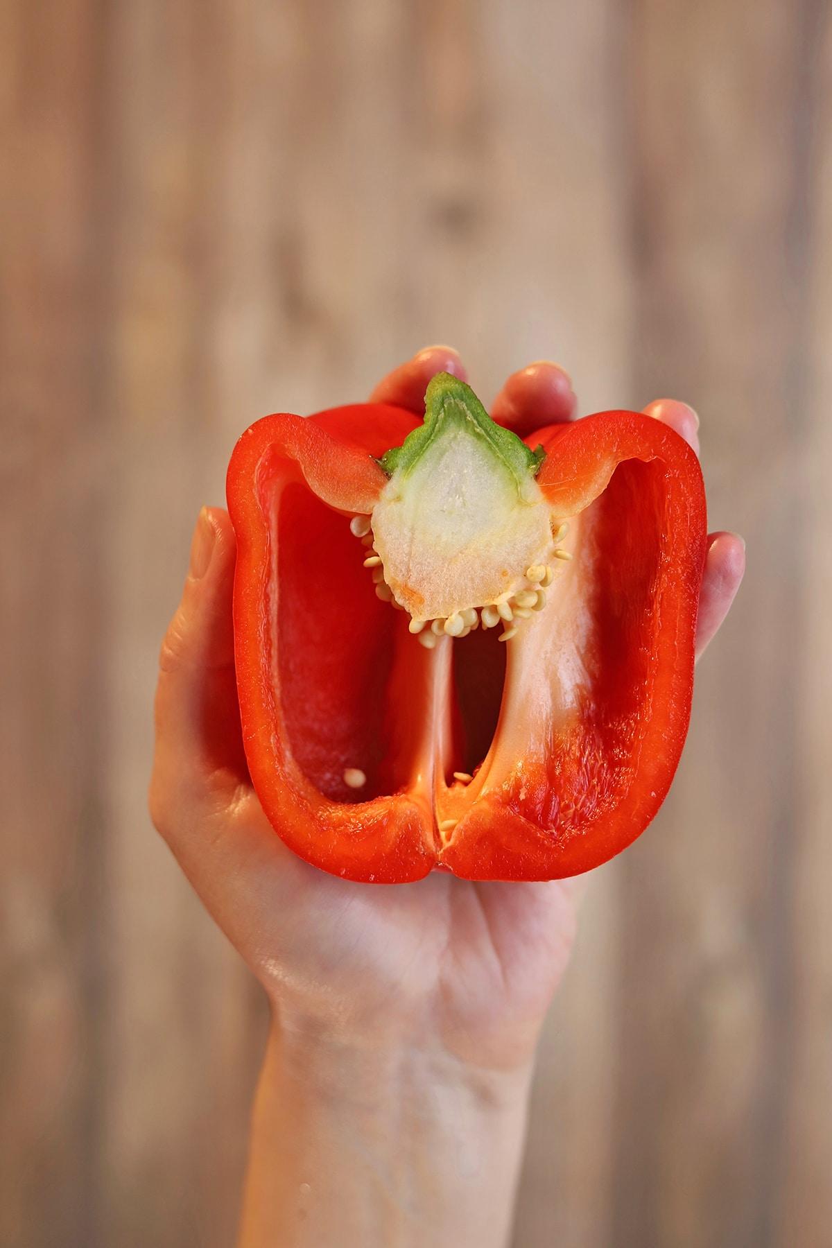 Hand holding bell pepper half over table.