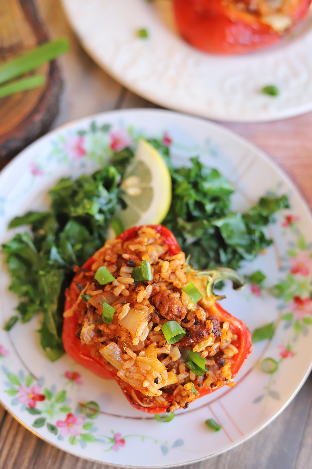 Stuffed bell pepper half on plate with sauteed kale.