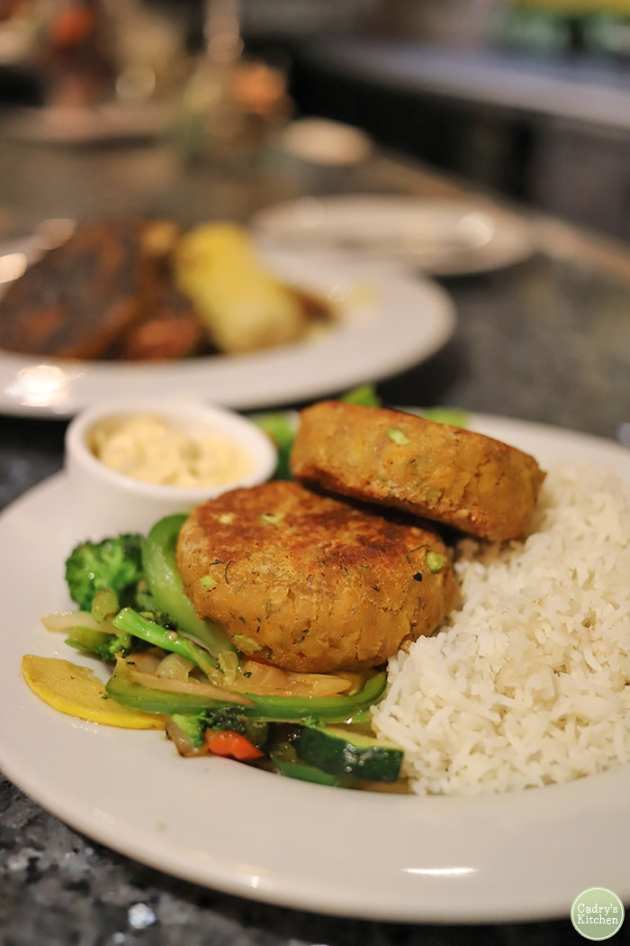 Chickpea crab cakes with rice and vegetables on plate at Ethos.