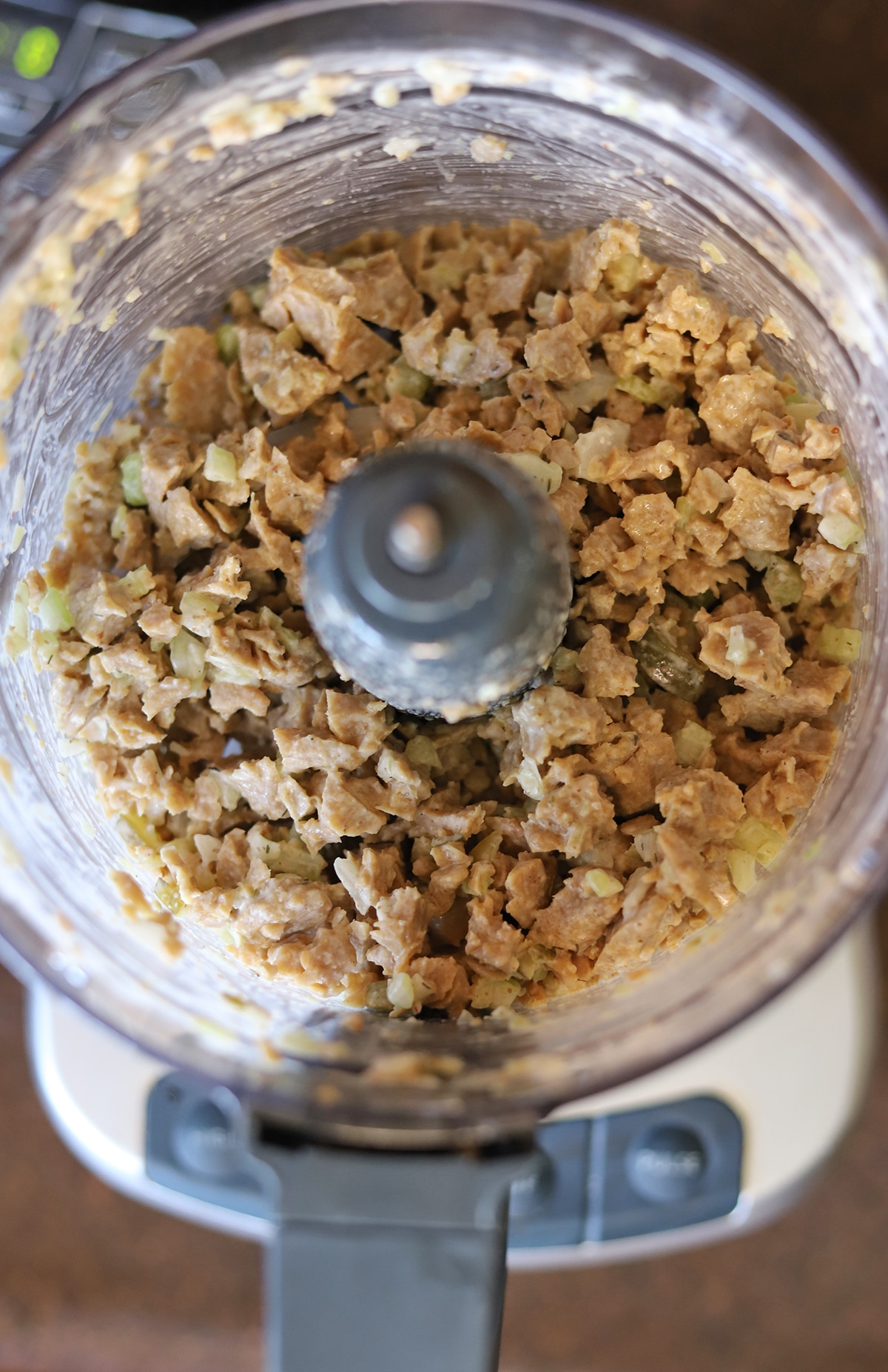 Chopped mock chicken salad in food processor bowl.
