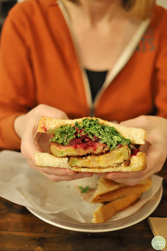 Hands holding fried green tomato sandwich