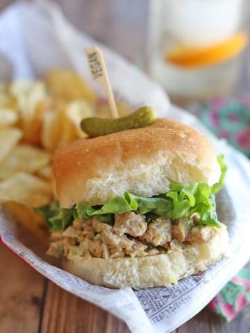 Vegan chicken salad sandwich in basket with potato chips.
