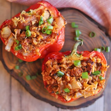 Bell pepper halves on cutting board, stuffed with rice, sausage, onions, and marinara.