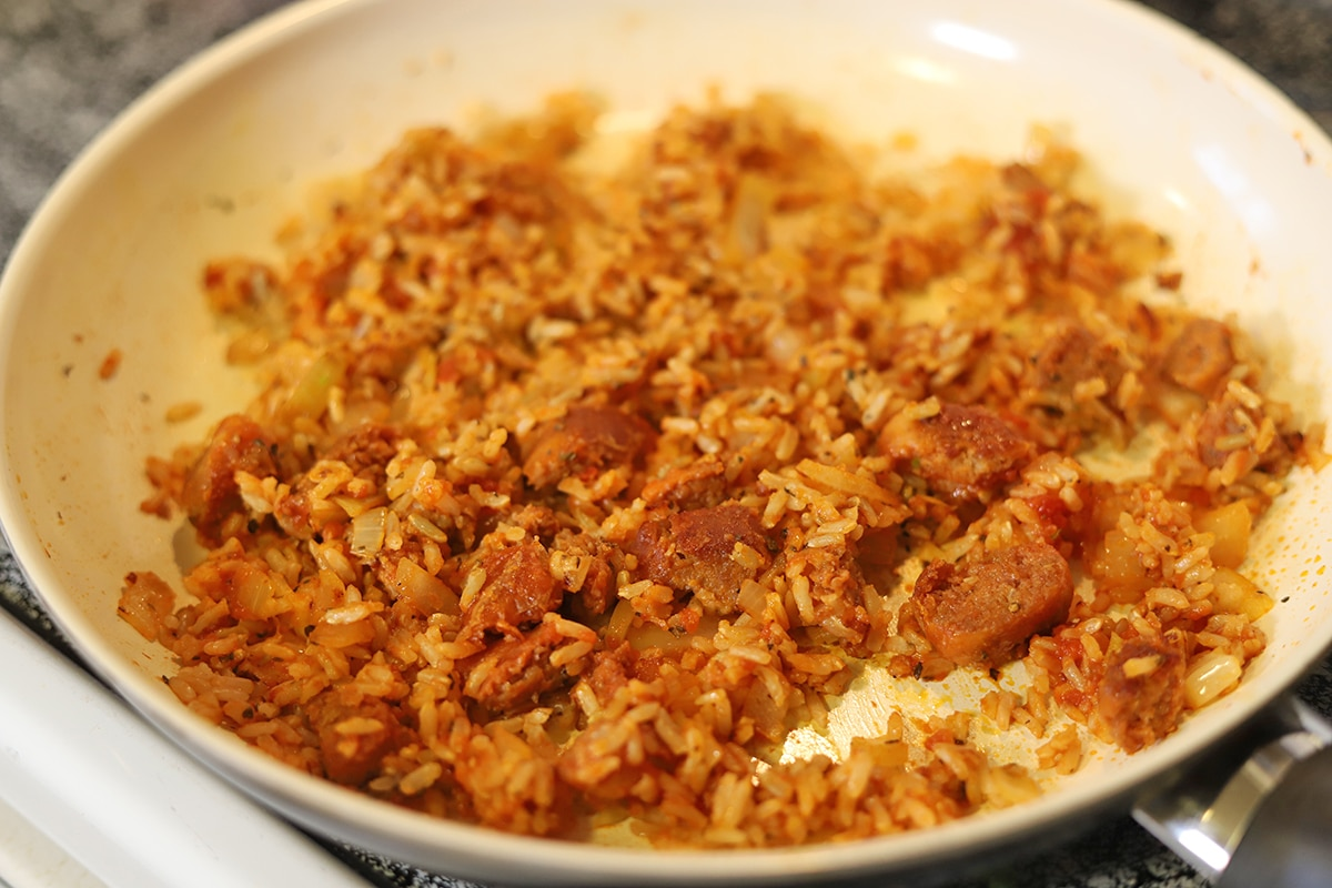 Rice, Beyond Meat sausage, onions, and garlic in skillet.