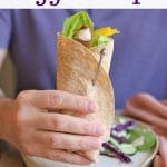 Text overlay: Vegan chick'n veggie wraps. Hand holding wrap in front of plate with salad.