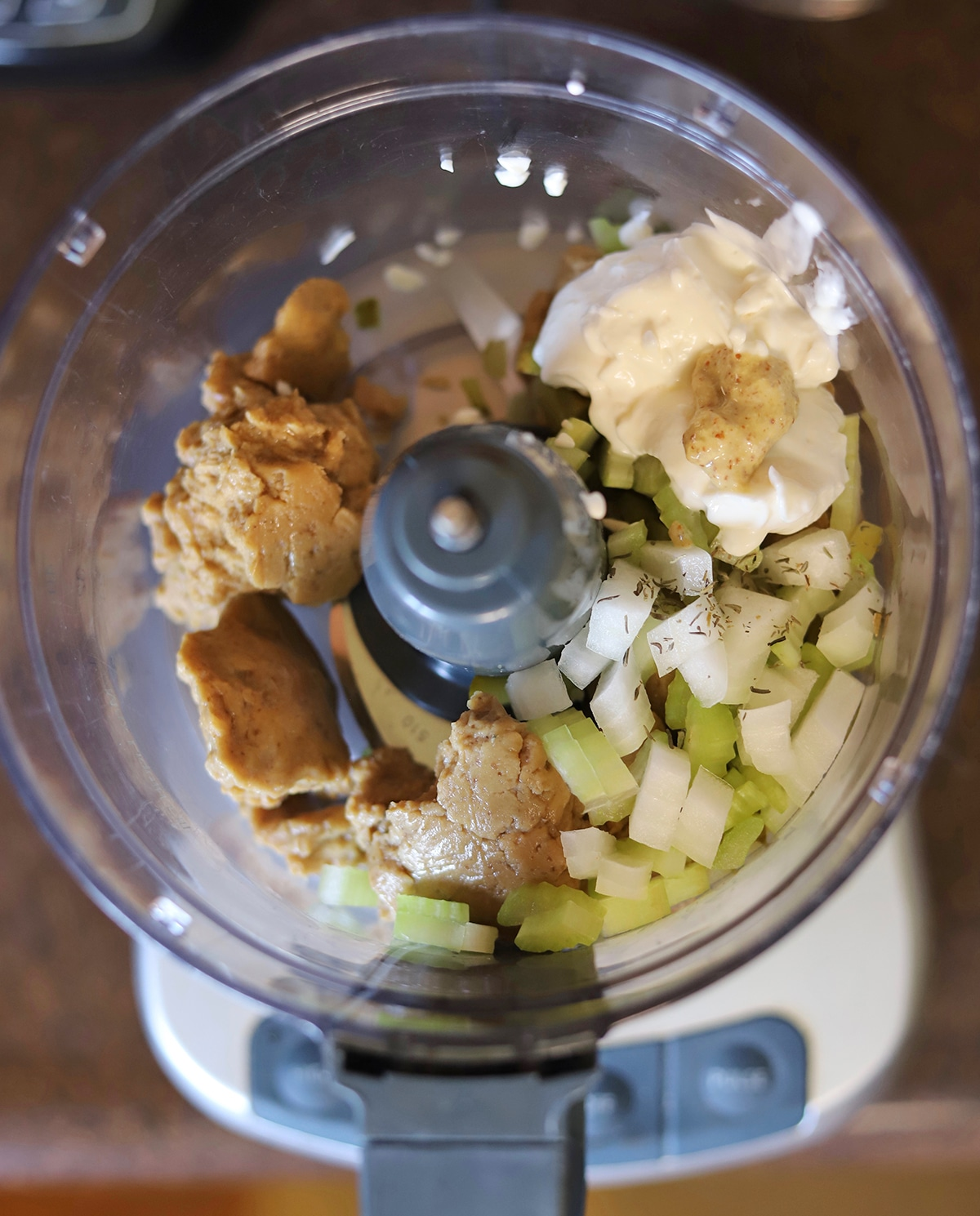Overhead food processor with seitan, mayonnaise, mustard, celery, and onions.