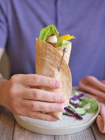 Hand holding tortilla wrap.