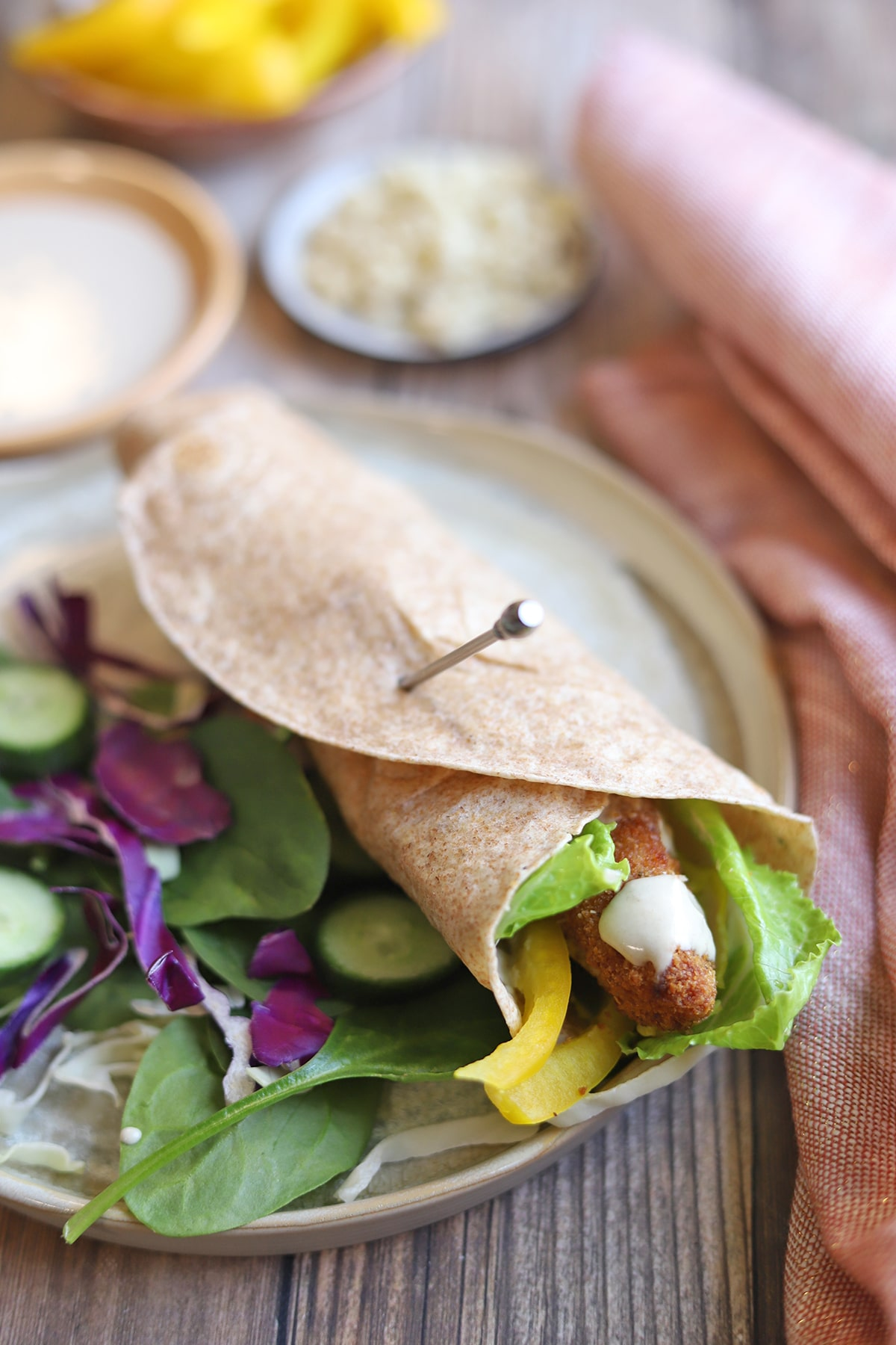 Vegan wrap with chick'n strips on plate by salad.