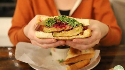 Hands holding fried green tomato sandwich.