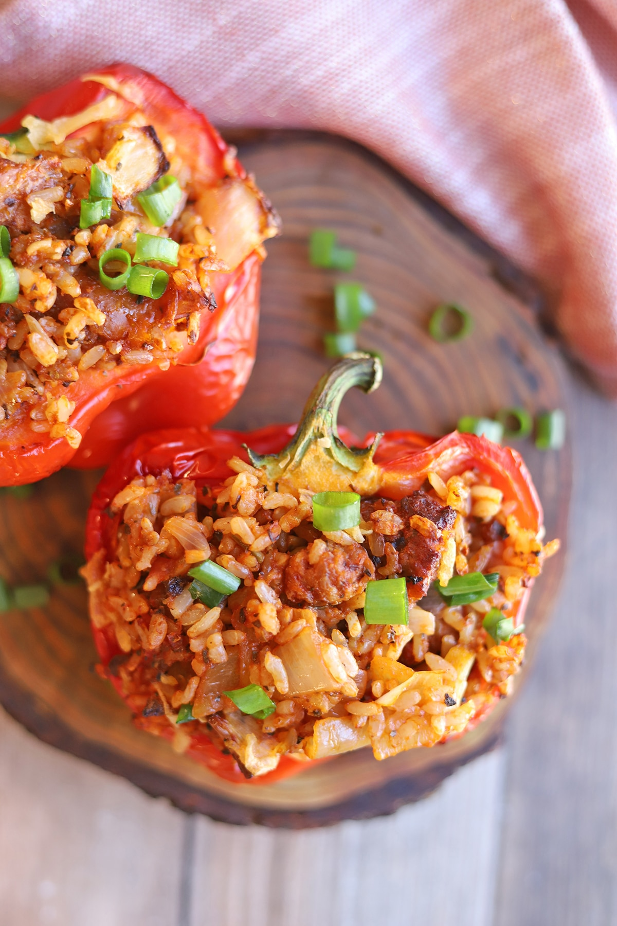 Bell pepper halves on cutting board, stuffed with rice, sausage, onions, and garlic.