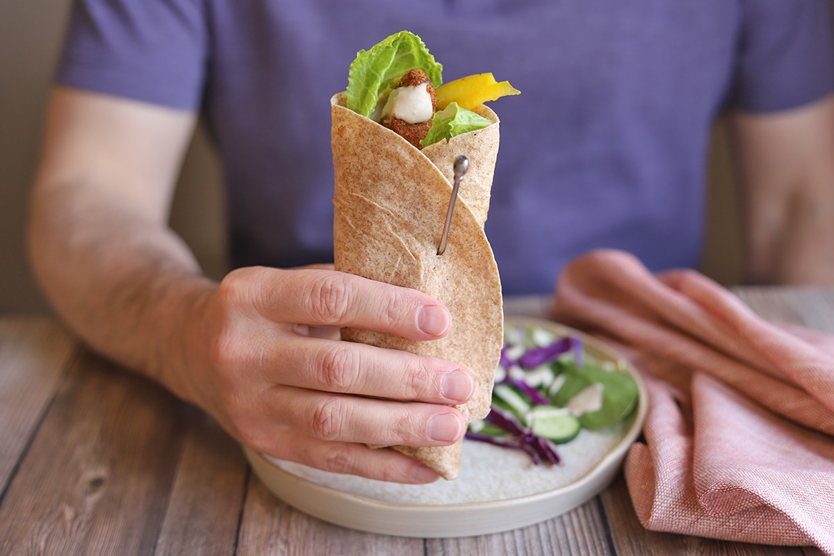 Hand holding veggie wrap by plate with salad.