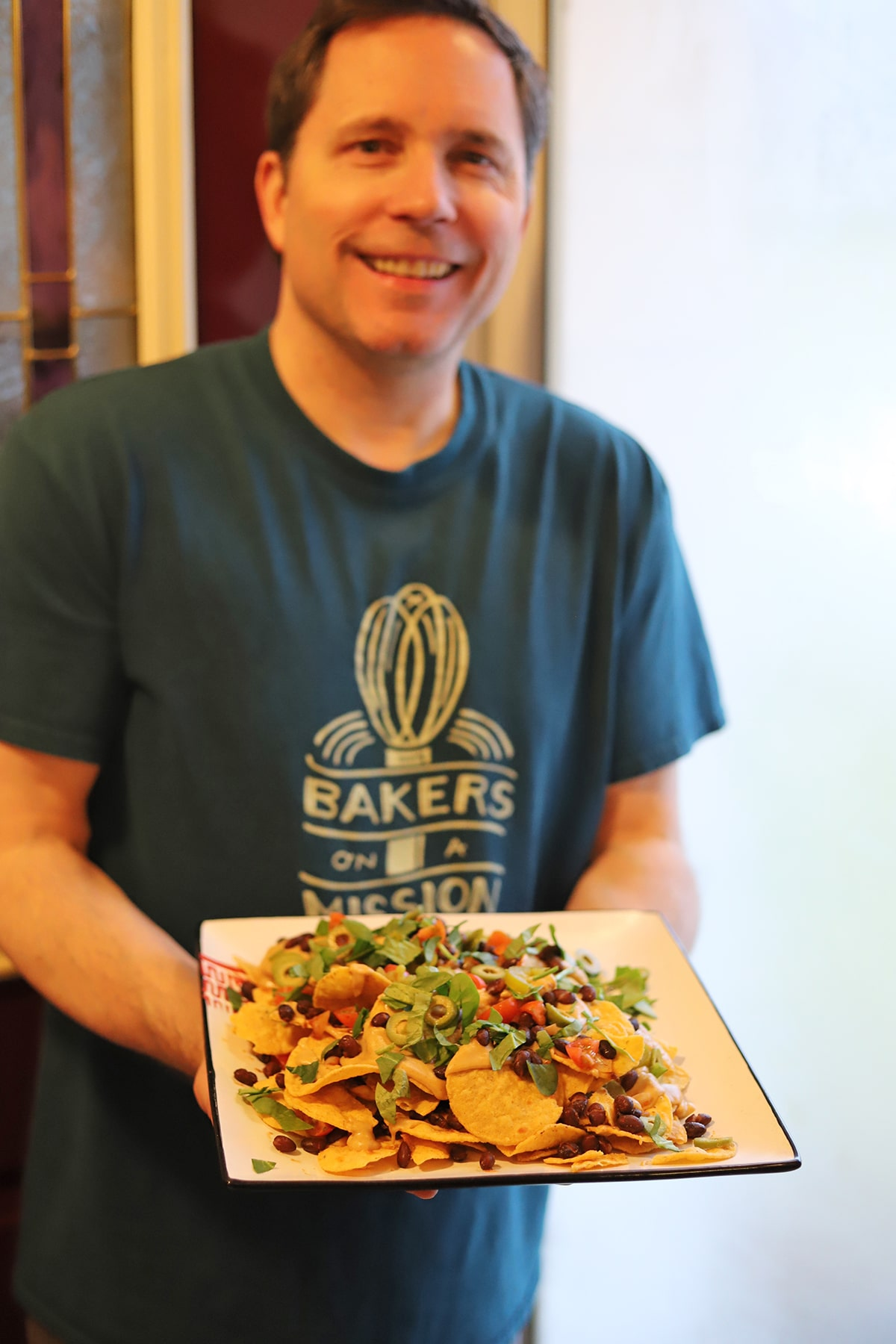 David holding platter of nachos.