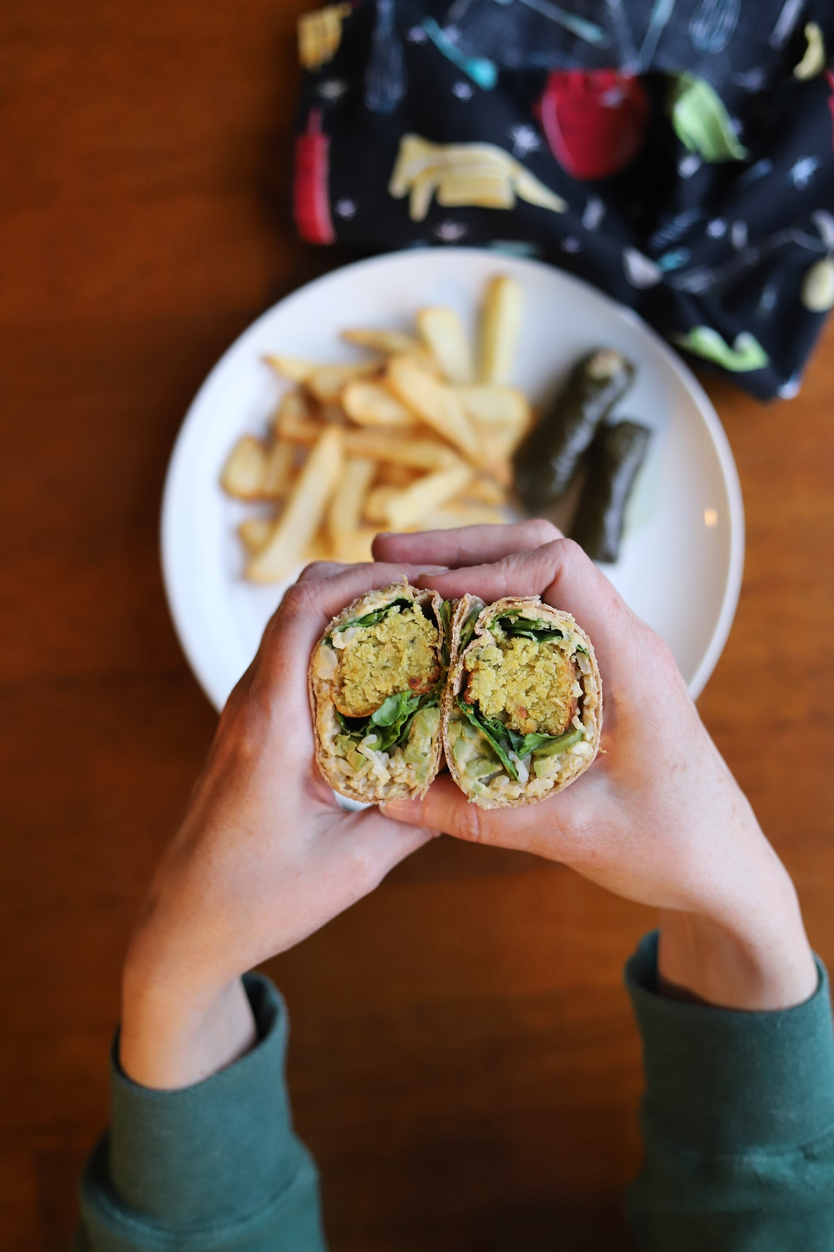 Hand holding falafel wrap with spinach, rice, and hummus.