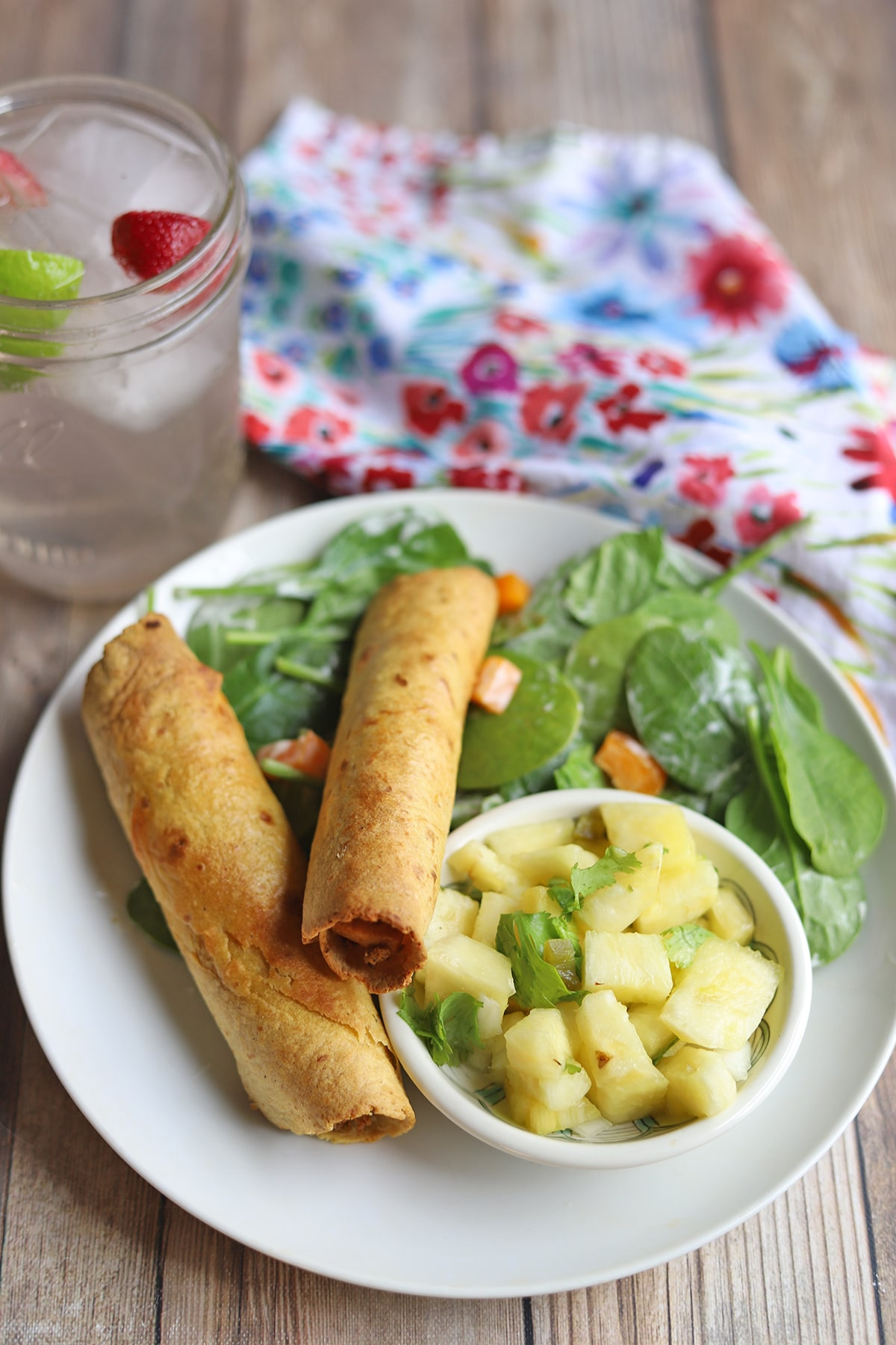 Jackfruit taquitos on plate with spinach salad and pineapple salsa.