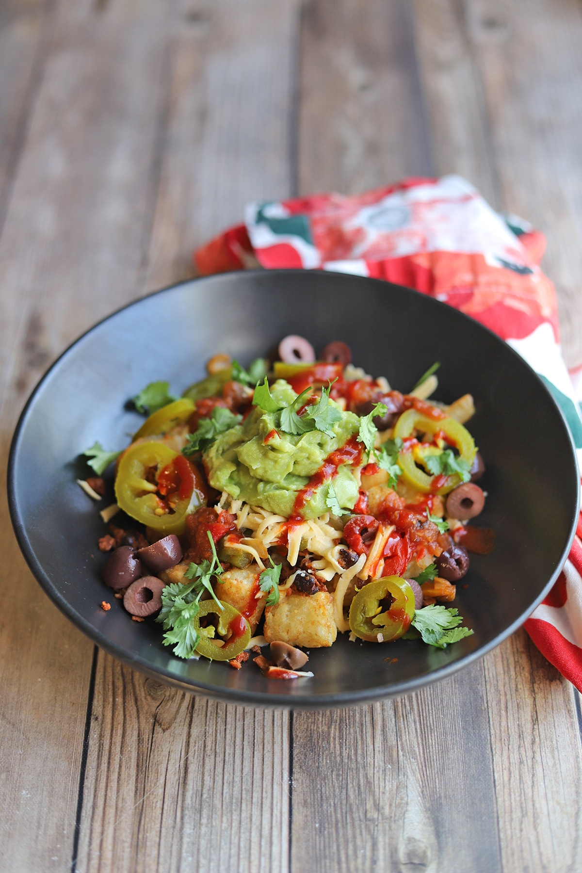 Tater totchos in bowl with non-dairy chese, guacamole, and hot sauce.