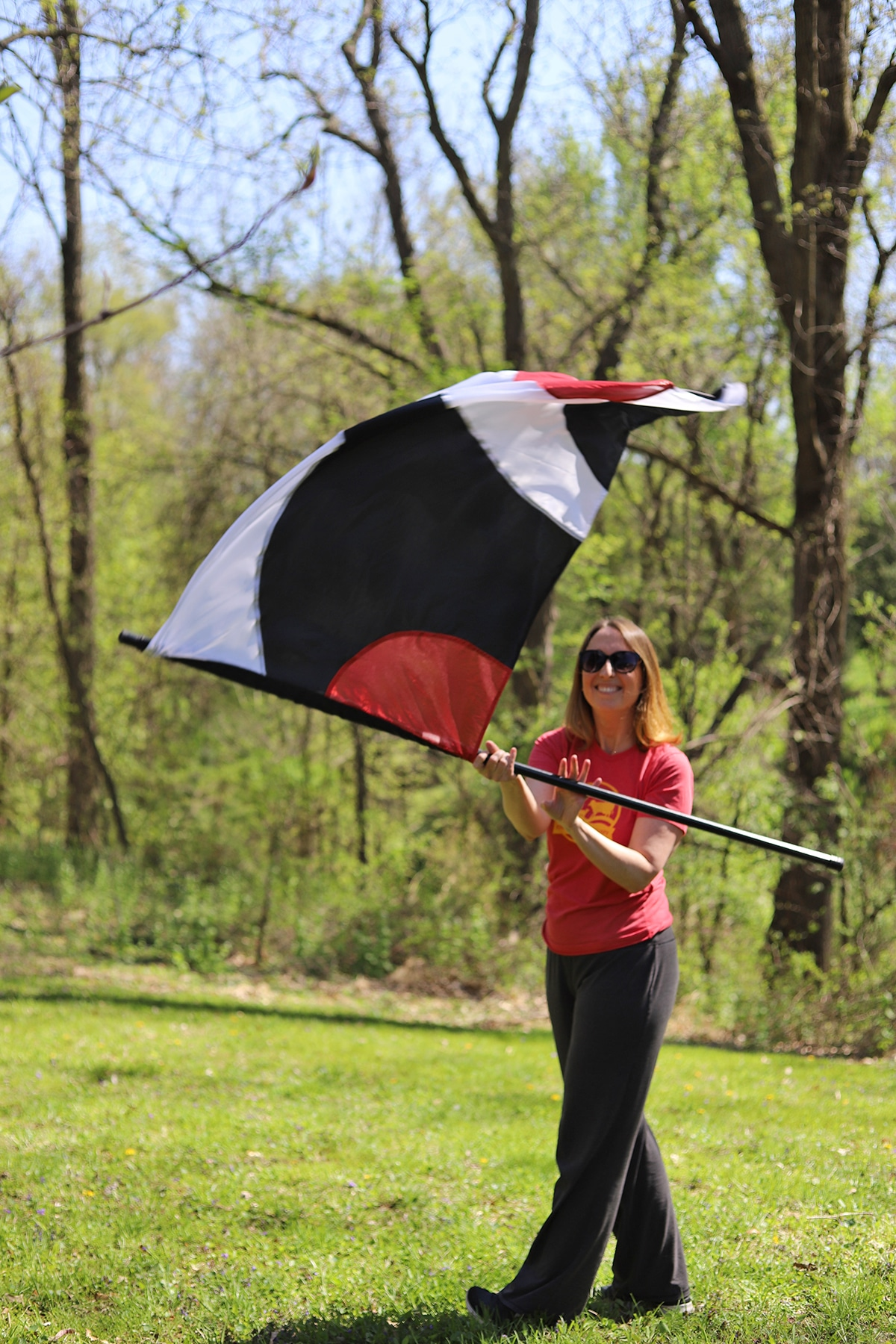 Cadry twirling a flag in the yard.