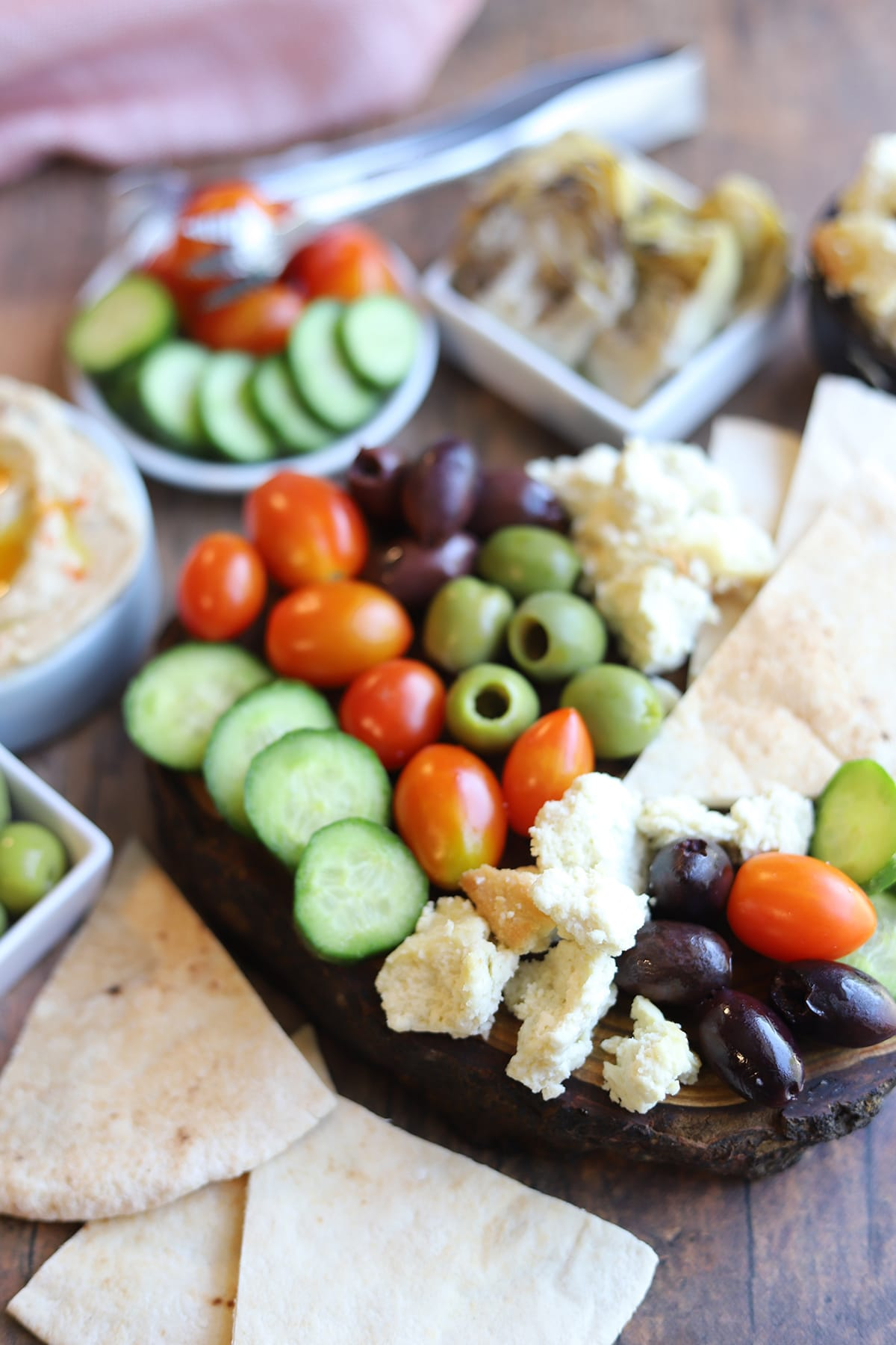 Mezze platter with cucumbers, tomatoes, vegan feta, and hummus.