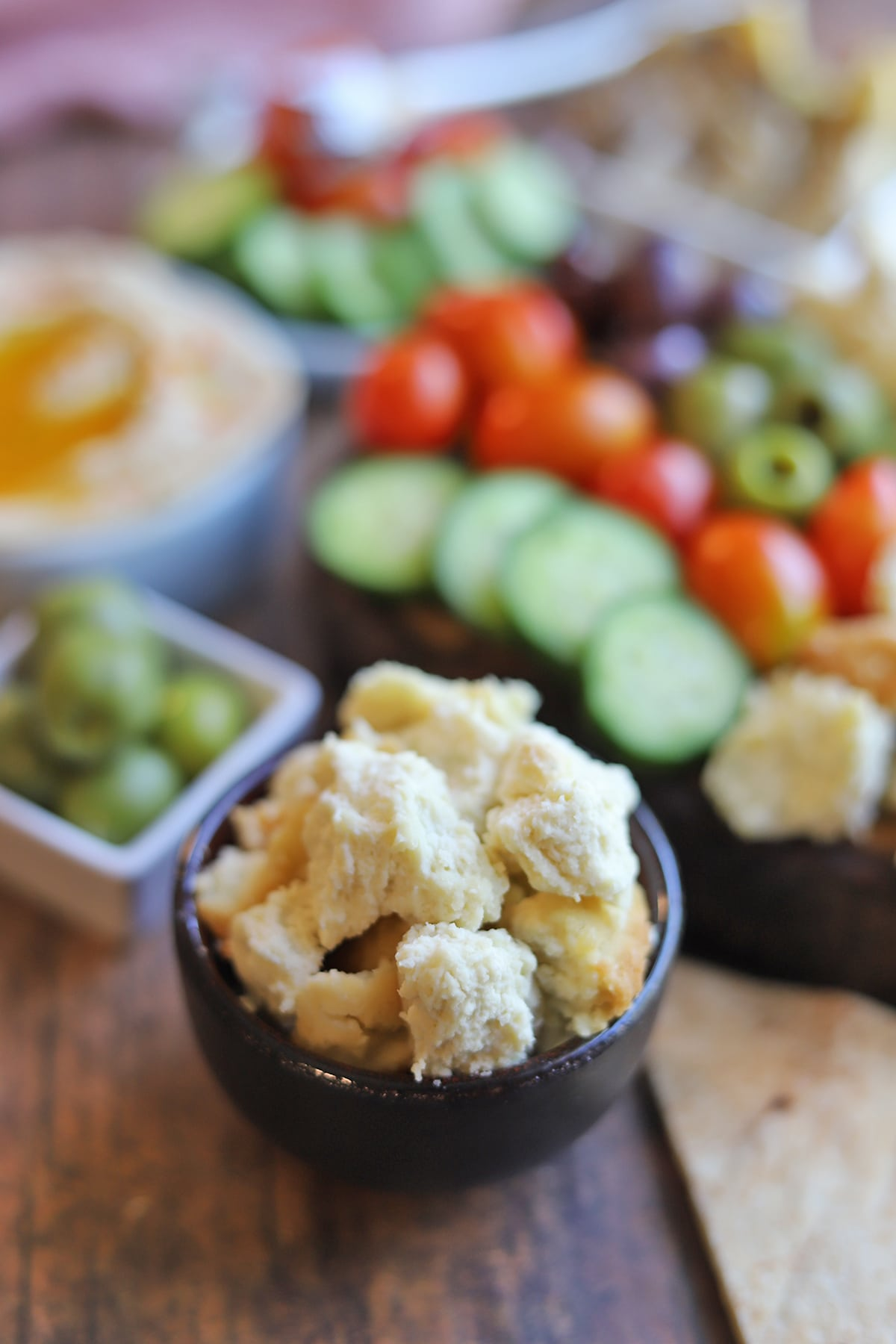 Crumbled almond feta in bowl by mezze platter.