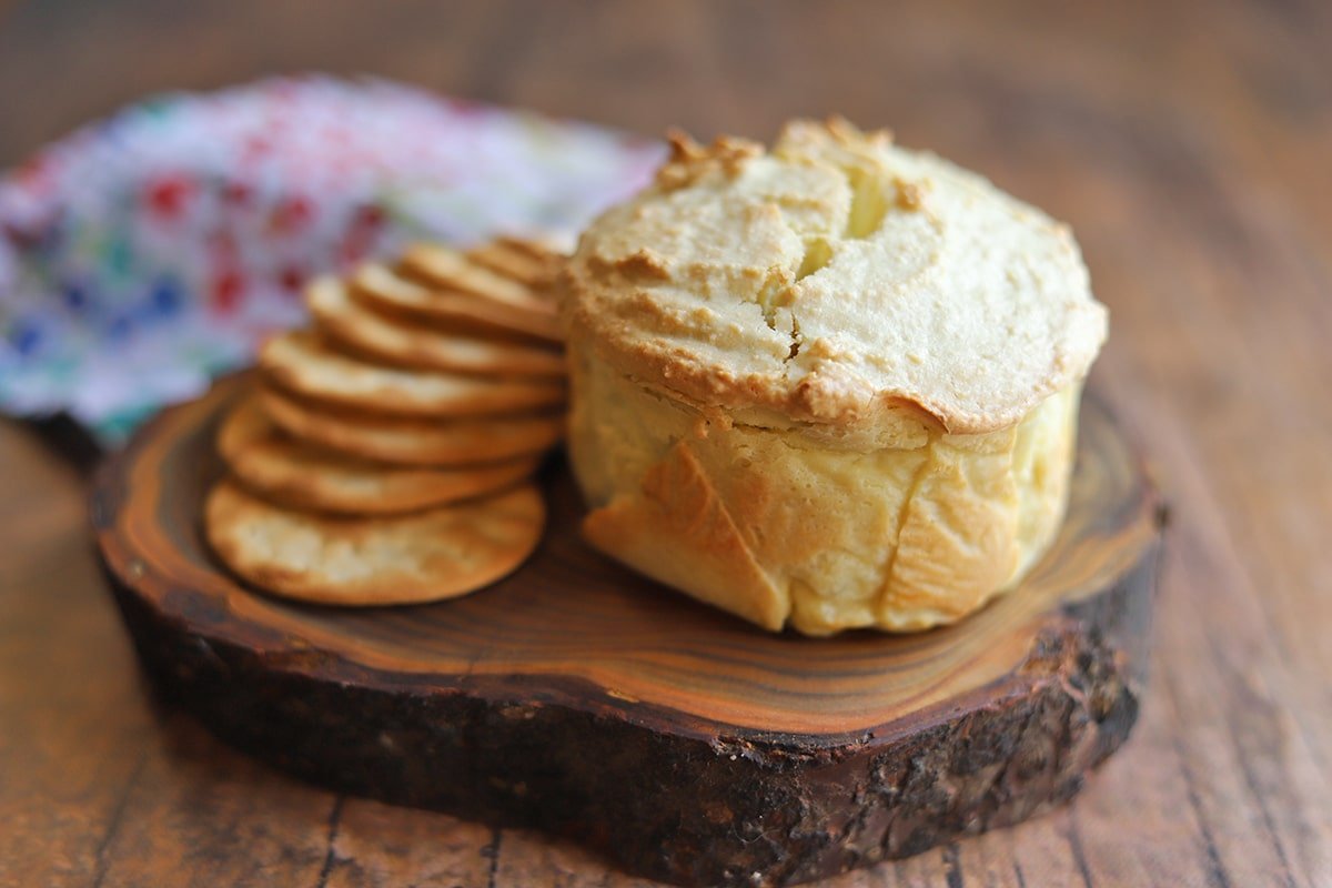 Baked almond feta with crackers on board.