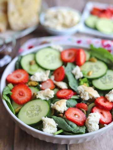 Bowl of salad with cucumbers, strawberries, and almond feta.
