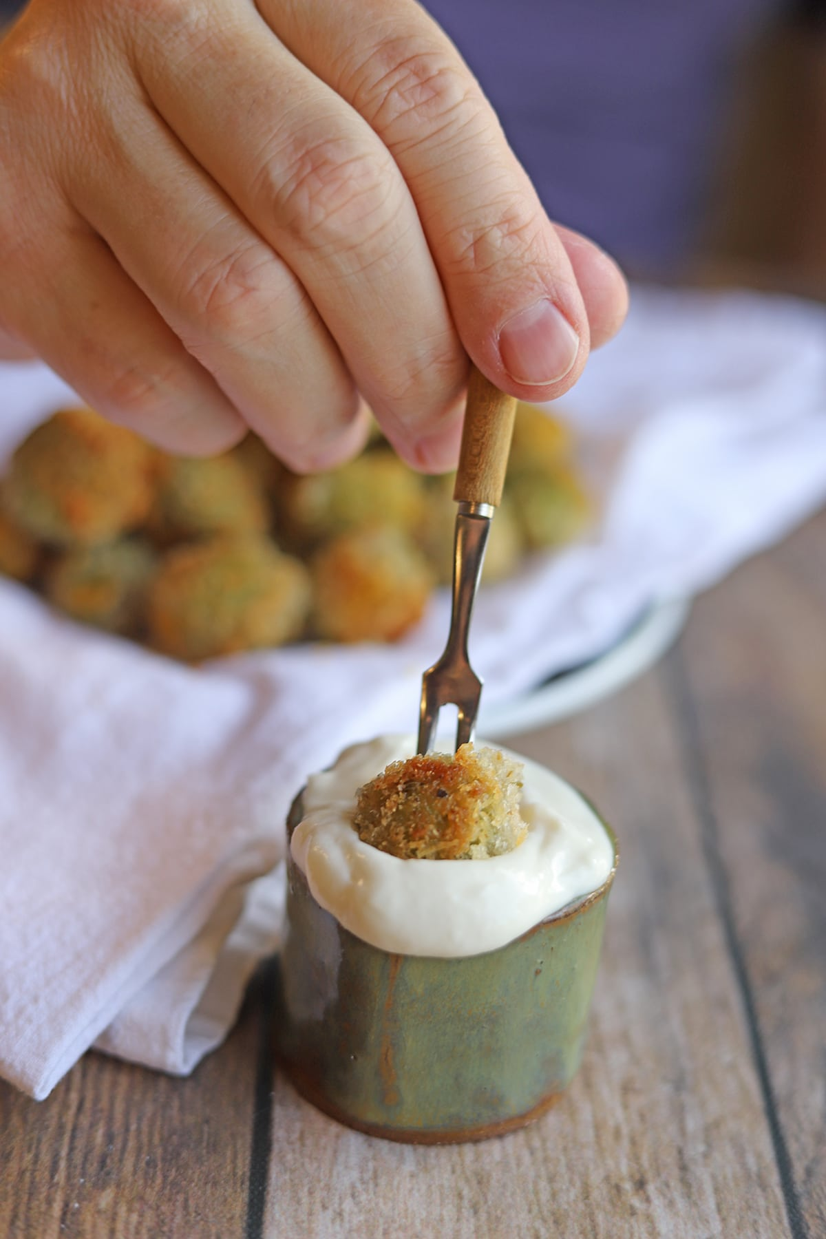 Breaded olive being speared with a tiny fork.